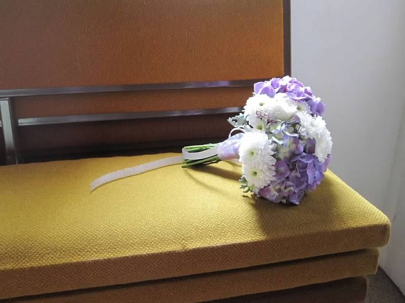 Lovely bouquets of purple hydrangeas, white roses, and other various white flowers, tied with silver ribbon.